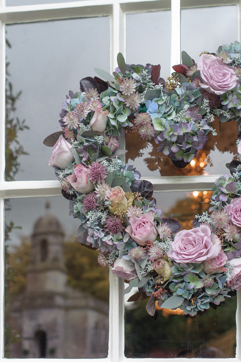 Heart shaped wreath by Passion with St Margaret's Chapel reflected in the window