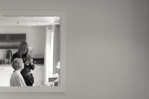 Bride looks out the window as he makup is applied in the South Farm bridal suite